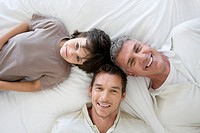 Portrait of grandfather and father lying on bed