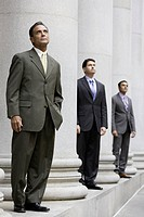 Three businessmen standing between columns