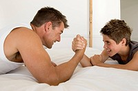 Father and son 12_13 arm wrestling on bed