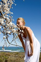 Young woman in summer dress smelling flower by sea