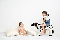 A baby is sitting on floor,girl rides on cow