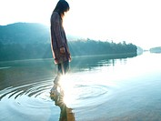 Woman standing in the water of lake in the morning