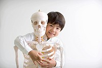 A boy is holding human skeleton,white background