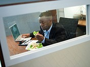 Businessman eating a salad at his desk