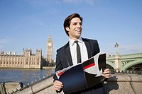 Happy young businessman with book standing against Big Ben clock tower, London, UK