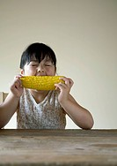 Girl having a big mouthful of corn