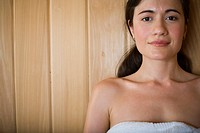 Portrait of a young woman smiling and relaxing in a sauna