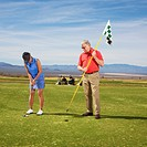 Woman putts as man holds flag pole