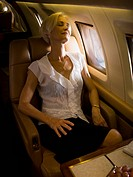 A senior woman sleeping in an airplane