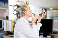 Woman with curlers in hair putting on makeup