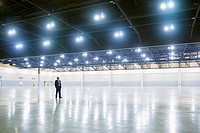 Hispanic businessman standing in empty warehouse