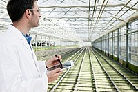 Germany, Bavaria, Munich, Scientist in greenhouse with digital tablet examining bed with seedlings