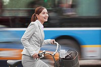 Chinese businesswoman riding bicycle in traffic