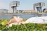 Germany, Cologne, Young woman relaxing in grass