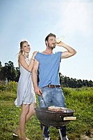 Germany, Cologne, Young couple grilling sausage and drinking beer
