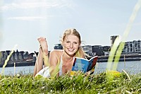 Germany, Cologne, Young woman reading book, smiling, portrait
