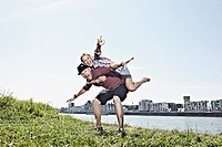 Germany, Cologne, Man giving woman piggyback ride