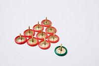 Red thumbtacks with one green on a white background