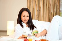 Woman reading a magazine over breakfast