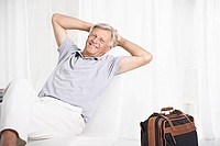 Spain, Senior man waiting in lobby with suitcase