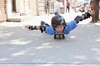 Caucasian boy laying on skateboard on sidewalk
