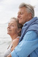 Spain, Senior couple on beach at Atlantic, smiling (thumbnail)