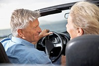 Spain, Senior couple looking at each other in convertible car