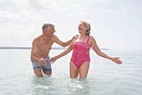 Spain, Senior couple swimming in beach at Atlantic