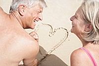 Spain, Senior couple on beach drawing heart in sand, smiling