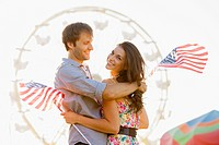 Caucasian couple holding American flags and enjoying carnival