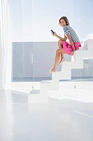 Spain, Mid adult woman sitting on stairway with cell phone