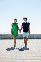 Spain, Mid adult couple walking on pavement