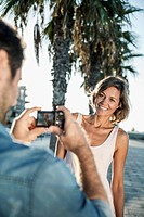 Spain, Mid adult man taking photograph of woman