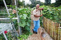 Black man leaning on shovel in community garden