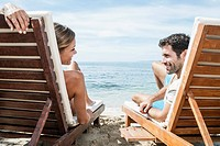Spain, Mid adult couple relaxing on beach chair