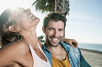 Spain, Mid adult couple sitting on bench, smiling