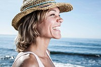 Spain, Mid adult woman with straw hat at Atlantic Ocean, smiling