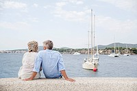 Spain, Senior couple sitting at harbour (thumbnail)