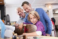 Germany, Leipzig, Grandfather, father and son repairing skateboard
