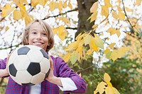 Germany, Leipzig, Boy playing football under autume tree