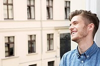 Germany, Berlin, Young man looking away, smiling