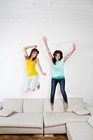 Germany, Berlin, Young women having fun and jumping on couch