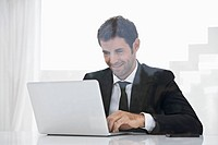 Spain, Businessman using laptop, smiling