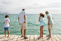 Spain, Grandparents with grandchildren standing on jetty, looking into water