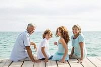 Spain, Grandparents with grandchildren sitting on jetty, smiling, portrait