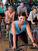 Female trainer with group on exercise bikes, portrait