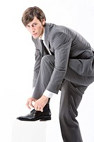 Businessman tying shoes, close up