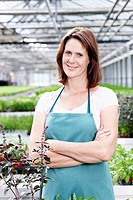 Germany, Bavaria, Munich, Mature woman in greenhouse, smiling, portrait