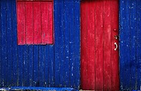A painted red door and window cover on a blue wooden building, st abb's head scottish borders scotland