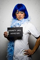 Mug shot of man in dress and feather boa